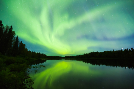 sunspot: Colorful Nortehrn lights on the sky above river in Lapland