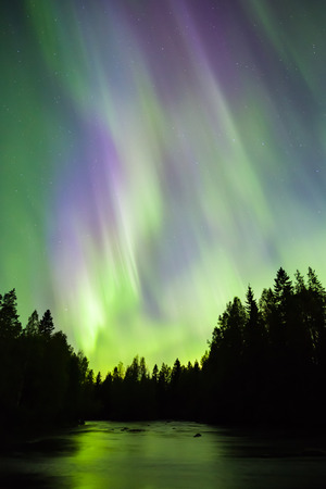 sunspot: Colorful Northern lights (Aurora borealis) in the sky by the river