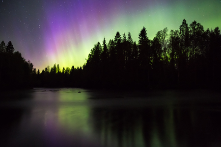 reflect: Colorful Northern lights (Aurora borealis) in the sky by the river