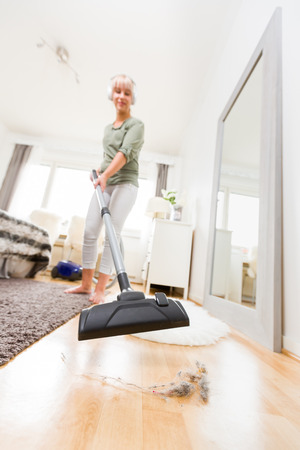 Young woman vacuuming floor listening music