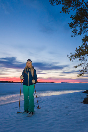 downshift: Young beautiful woman snowshoeing by the lakeside