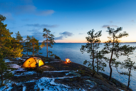 downshift: Campfire and tent in wilderness by the lakeside at the sunset, snow on the ground Stock Photo