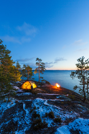 Campfire and tent in wilderness by the lakeside at the sunset, snow on the ground Stock Photo