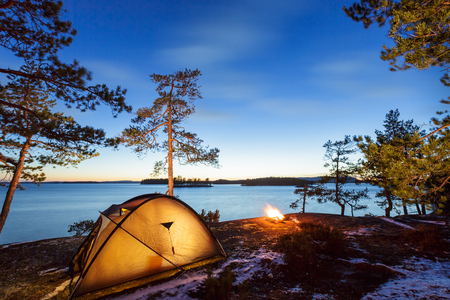 Campfire and tent in wilderness by the lakeside at the sunset, snow on the ground Фото со стока
