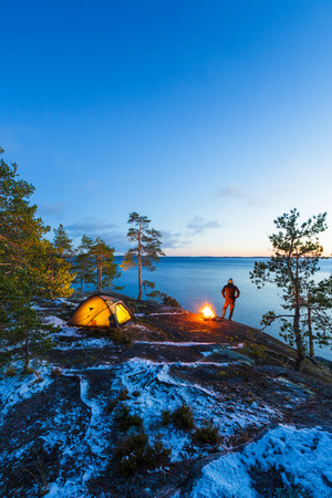 Man is standing around a campfire and just relaxing, snow on the ground