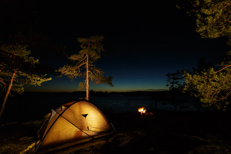 Campfire and tent in wilderness by the lakeside in the night