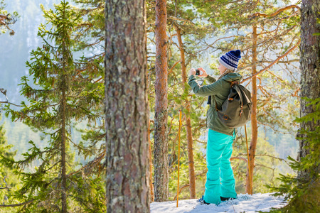 Young beautiful woman with snowshoes and mobile phone chill out and relax in the forest