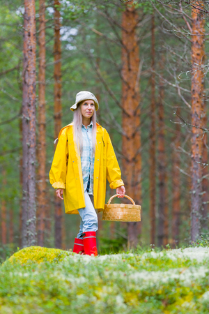 Beautiful young woman gathering mushrooms in forest  with basket