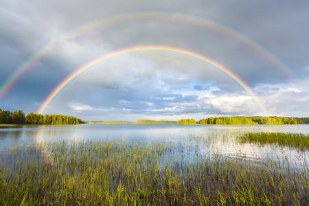 Regenboog in midzomer over het meer in mooi landschap in Finland.