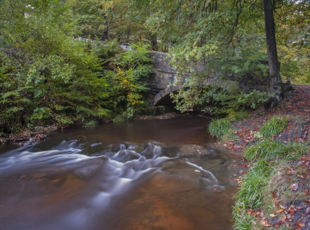 old packhorse bridge: old stone bridge in yorkshire autumn woodland Stock Photo