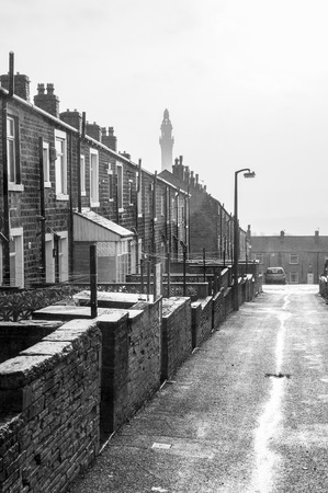 silhoutted: A rainy wet day in Yorkshire showing a typical Victorian terraced street leading towards a folly named Victorian Wainhouse Tower silhoutted by a misty sky.