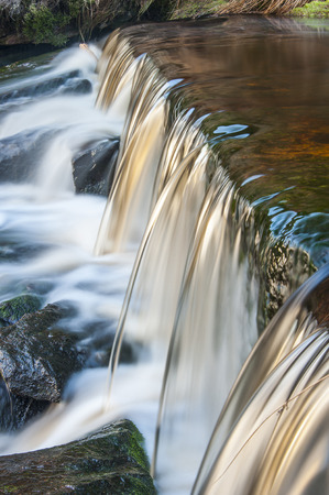 beck: A small moorland stream cascading over a weir captured using a slow shutter speed to blur the movement of the water.