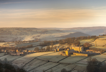 north yorkshire: Standing on a hillside in Yorkshire is this formwr Victorian textile mill which has been transformed in to new fashionable apartments.The shot was taken on a frosty winters morning at sunrise Stock Photo