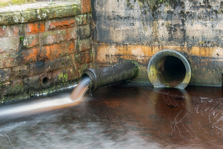 spewing: An overflow pipe at a water treatment works spewing water in to a stream