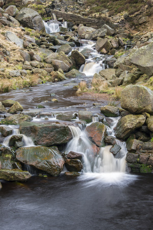 tumbling: A small stream tumbling over fallen millstone grit blocks in a valley in the Northern Peak District area of Saddleworth close to Holmfirth. Stock Photo