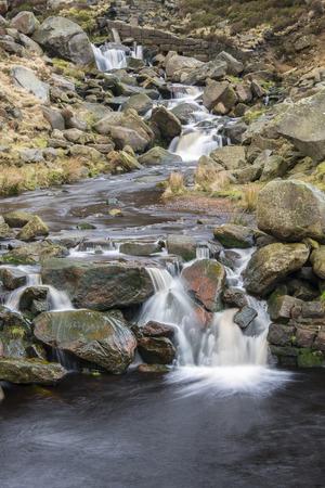 grinta: Un piccolo ruscello cadendo su blocchi di pietra molare caduti in una valle nella zona nord Peak District di Saddleworth vicino a Holmfirth.