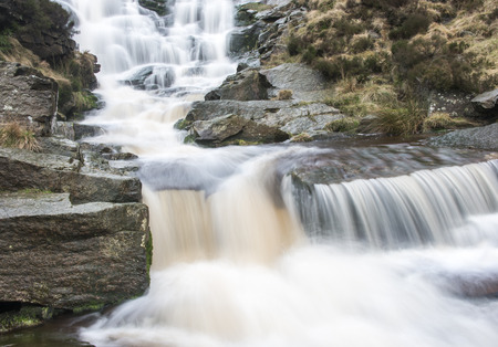 grit: Water cascading over millstone grit boulders on a stream in the peak district national park. Stock Photo