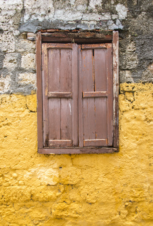 plasterwork: Traditional window and shutters against a plastered yellow wall greece Stock Photo