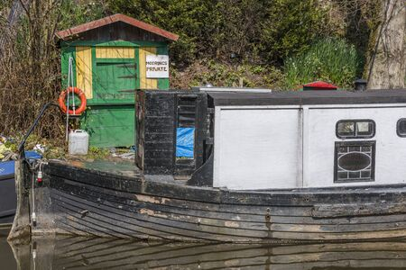 untidy: A narrowboat moored alongside some untidy garden items Stock Photo