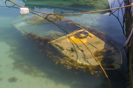 sunken boat: A sunken motor boat lies submerged in a small harbour on the Greek island of Rhodes