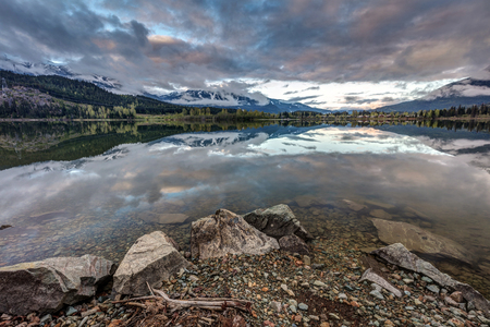 Sunrise from the shores of a very calm green lake in Whistler Blackcomb resort, British Columbia, Canada.