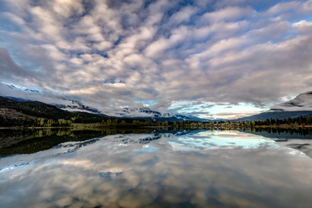 Perfect reflection of whistler, blackcomb breaking through the clouds from the shores of Green lake at sunrise in Whistler, British Columbia, Canada