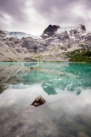 A rock piercing the calm surface of the beautiful turquoise upper Joffre Lake. The lake is fed by Matier Glacier next to Mount Joffre in the natural beauty of British Columbia, Canada