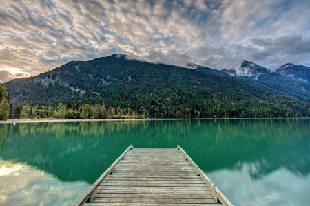Sunrise viewed from the dock at Birkenhead Lake Provincial Park, with emerald colored water and reflection, tall mountains with a fresh dusting of snow and cool cloud formations.