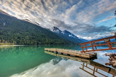 Reflection of the dock at Birkenhead Lake on a calm morning. Green water, tall mountains, fresh dusting of snow on the peaks and cool clouds at sunrise in the remote wilderness of Birkenhead Lake Provincial Park, British Columbia, Canada.