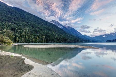 Beautiful calm reflection from the beach of Birkenhead lake at sunrise, Birkenhead lake provincial park, British Columbia, Canada.
