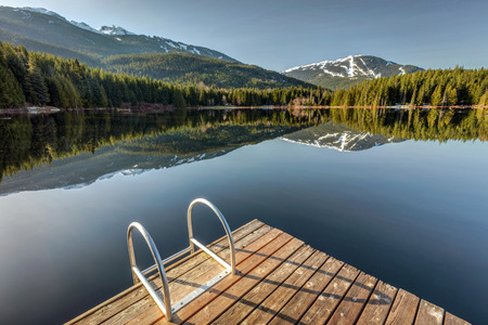 Early morning sunlight on the dock at Lost Lake in Whistler, British Columbia, Canada Stock Photo