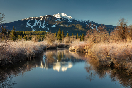 Serenity of the River Of Golden Dreams on a beautiful Spring morning with the reflection of Whistler Mountain. The sun just rose over the mountain and started illuminating the slightly frosted banks of the river. Whistler, British Columbia, Canada