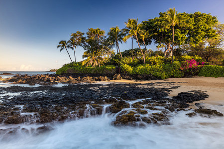 Lava Falls of Paako Cove in South Maui, Hawaii. Waves crashing on lava rocks on this idyllic beach.