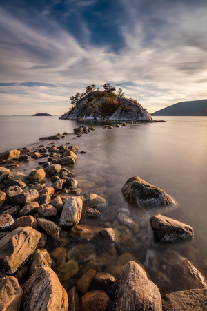 The path to Whyte island at sunset. Rock hoping to the island at high tide in Whytecliff Park, West Vancouver, BC 版權商用圖片