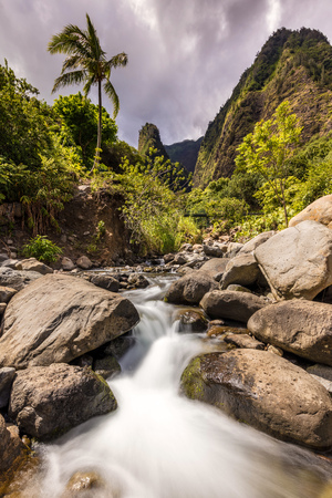 Lush Iao Valley Stream. Tropical scene with the Iao needle, a lone palm tree and long exposure of the lush stream down the valley on West Maui, Hawaii. 版權商用圖片