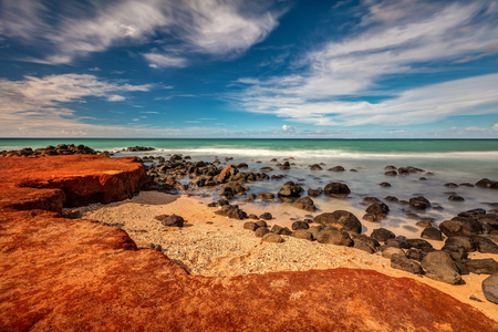 Maui Red Dirt at Baby Beach. Very colorful scene with the red dirt, gold beach, black lava rocks, green sea and blue sky. Maui, Hawaii.