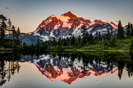 Last glow on the peak of mount Shuksan reflected in the very calm Picture Lake while on a day adventure, hiking at Mount Baker area in the state of Washington, Pacific Northwest, USA