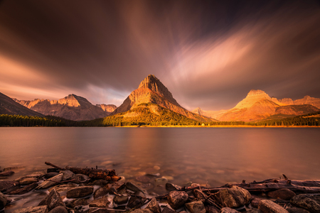 Sunrise in Glacier National Park. Long exposure with mount grinnell as a focal point at sunrise. clouds and smoke from forest fires created the dramatic effect. 版權商用圖片 - 104951928