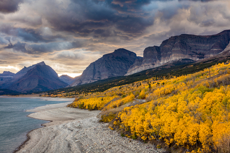 Dramatic sky in Autumn in Glacier National Park, Montana, USA. fall foliage in peak color on the shore of lake sherburne. clouds and smoke from forest fires created the drama in the sky at sunset