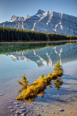 Little island illuminated with morning light on a calm two Jack Lake with reflections of Mount Rundle in Banff National Park, Alberta, Canada 版權商用圖片 - 104951932
