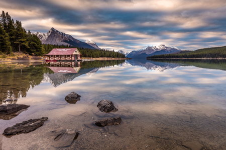 Maligne Lake Boat House reflection at sunrise in the wilderness of Jasper National Park, in the heart of the Canadian Rockies. 版權商用圖片 - 104951973
