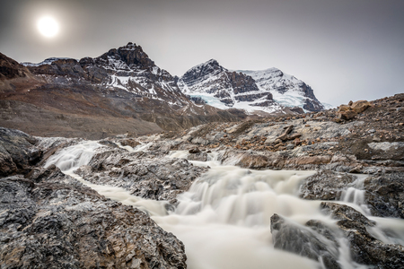 hazy sun and Silky melt water of Athabasca Glacier on the Icefield Parkway, Jasper National Park, Alberta, Canada