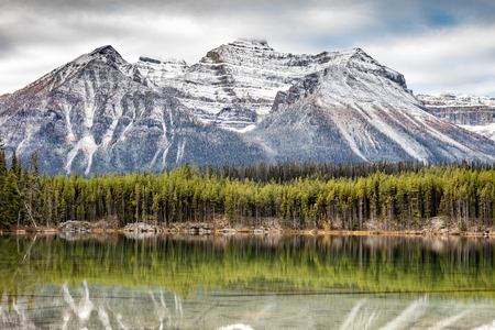 Fall in the Canadian Rockies. A dusting of snow on the tall rocky mountain peaks and reflection on a calm lake. this scene was captured in Banff National Park