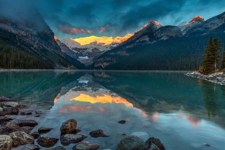 The First sunlight illuminating Victoria glacier on a calm morning in Autumn at Lake Louise in Banff National Park, Alberta, Canada. 版權商用圖片 - 104951983