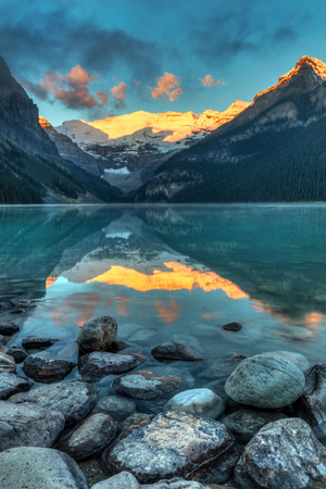the sun rising and illuminating victoria glacier with a perfect reflection in the turquoise water of Lake Louise in Banff National Park, Alberta, Canada. 版權商用圖片 - 104951985