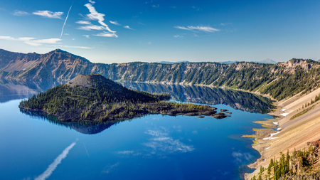 the Blue Jewel of Oregon. Deep blue lake inside a volcano with a stunning reflection of Wizard Island. Crater Lake National Park.
