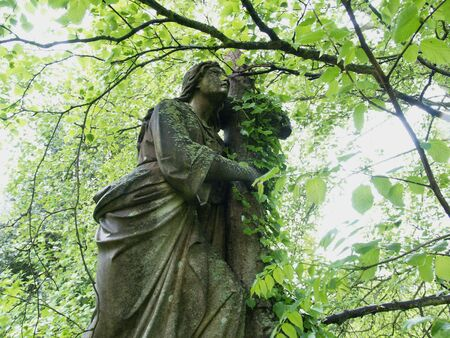 churchyard: A Victorian churchyard statue softened by nature Stock Photo