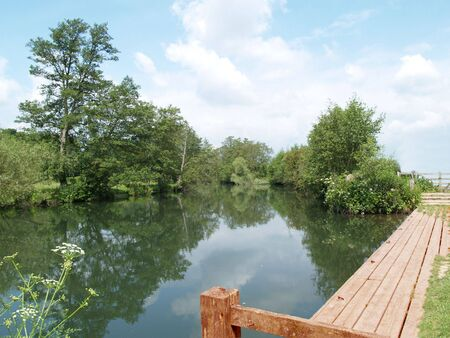 landing stage: A landing stage awaits boats and customers, and the river quietly flows Stock Photo