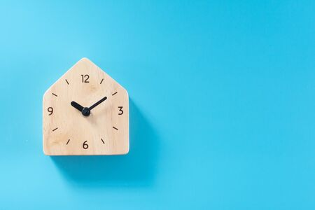 Wooden clock on blue background. 写真素材