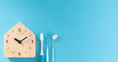 Wooden clock with dental tool on blue background.